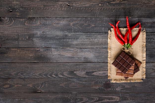 Chocolate negro y chocolate con leche con chiles rojos calientes espacio libre para texto Foto Premium
