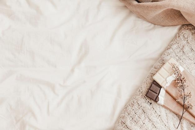 Chocolates con hierba y cuadros acostado en sábana blanca Foto gratis