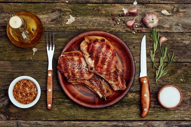Chuletas de cerdo a la parrilla en un plato con tenedor y cuchillo sobre una vieja mesa de madera. Foto Premium