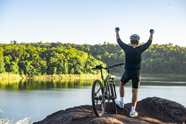 Ciclista de bicicleta de montaña de pie en la cima de una montaña con bicicleta Foto gratis
