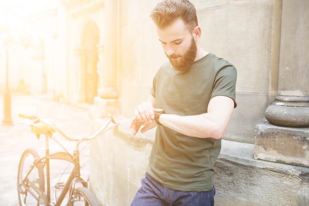 Ciclista masculino que mira tiempo en el reloj de pulsera Foto gratis