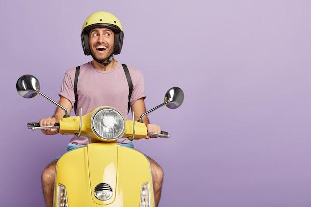 Ciclista o mensajero masculino feliz conduce scooter amarillo, usa casco protector, camiseta casual, posa en su propio transporte, mira con alegría a un lado, transporta algo, aislado en la pared púrpura, espacio en blanco Foto gratis