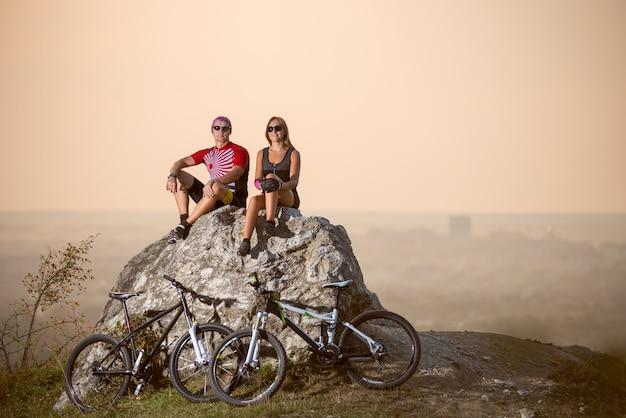 Los ciclistas están sentados en una gran piedra junto a ellos, son bicicletas deportivas. Foto Premium