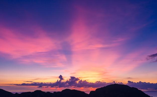 El cielo azul hermoso del paisaje crepuscular y la luz de pandora con primero plano de la silueta de la montaña en el mar en tailandia Foto Premium