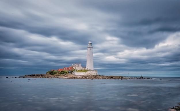 Cielo dramático sobre el faro de santa maría. paisaje marino de verano. whitley bay, inglaterra. gran bretaña Foto Premium