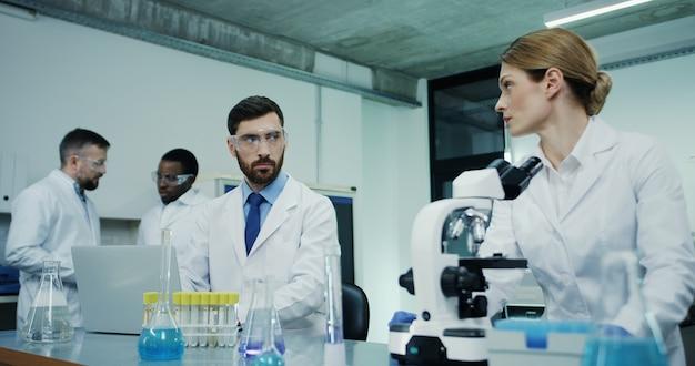 Científica caucásica en la túnica blanca mirando en el microscopio mientras investiga y su colega masculino prueba un poco de líquido en tubo en la computadora portátil Foto Premium