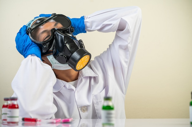 El científico se sentó con una máscara de gas, sosteniendo su mano sobre la cabeza. Foto gratis