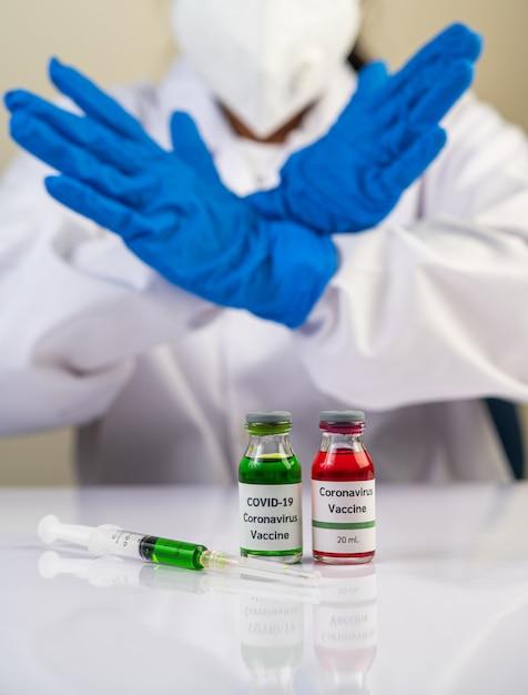Los científicos usan guantes azules y hacen que las manos sean una vacuna inaceptable para prevenir el covid-19 Foto gratis