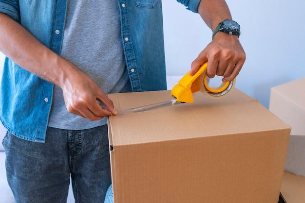 Cierre para arriba de la caja de cartón del embalaje de la mano masculina Foto Premium