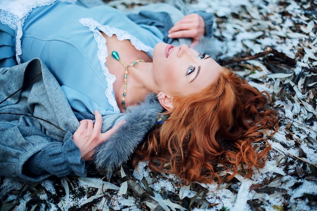 El cierre - para arriba de una chica joven hermosa con el pelo rojo y los ojos azules que mienten en la nieve mira el cielo en parque de la primavera. Foto Premium