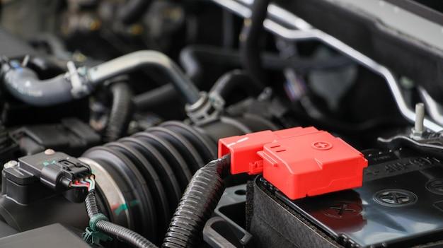 Cierre la batería del automóvil con el motor del automóvil. Foto Premium