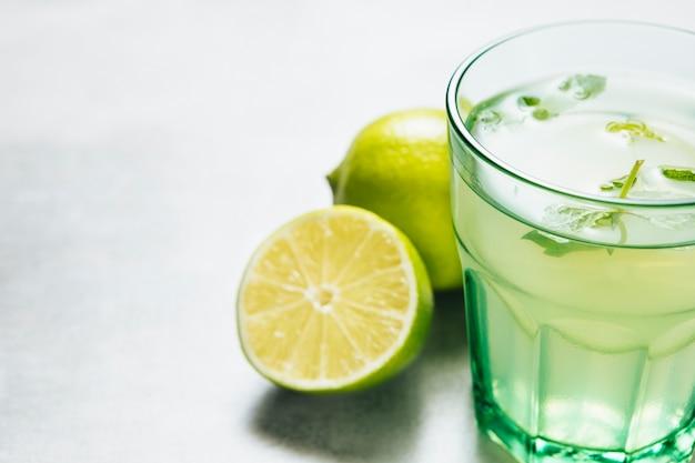 Cierre plano de vaso de limonada sobre fondo liso Foto gratis
