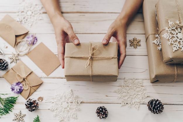 Ciérrese para arriba de la caja de regalo del presente de la mujer de las manos en la tabla de madera con la decoración de navidad. Foto Premium