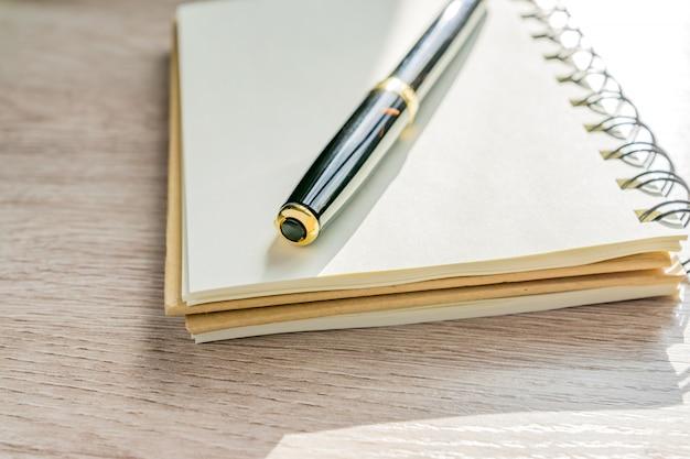 Ciérrese para arriba del cuaderno y de la pluma vacíos de kraft en la tabla de madera Foto Premium