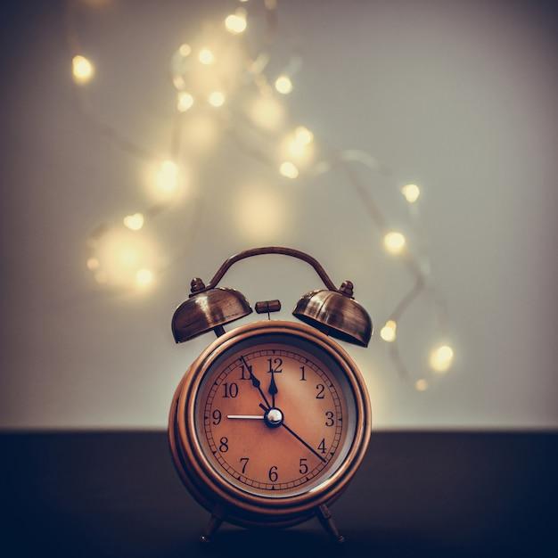 Ciérrese para arriba del despertador retro en fondo borroso de la navidad con el bokeh ligero Foto Premium