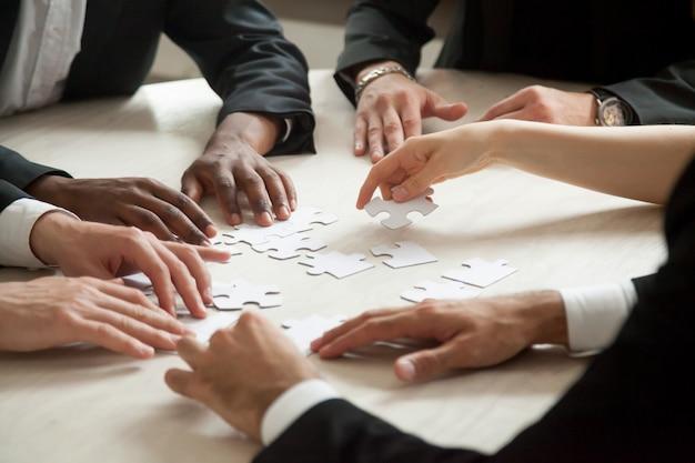 Ciérrese para arriba del equipo multiétnico que soluciona el juego en blanco del rompecabezas. Foto gratis