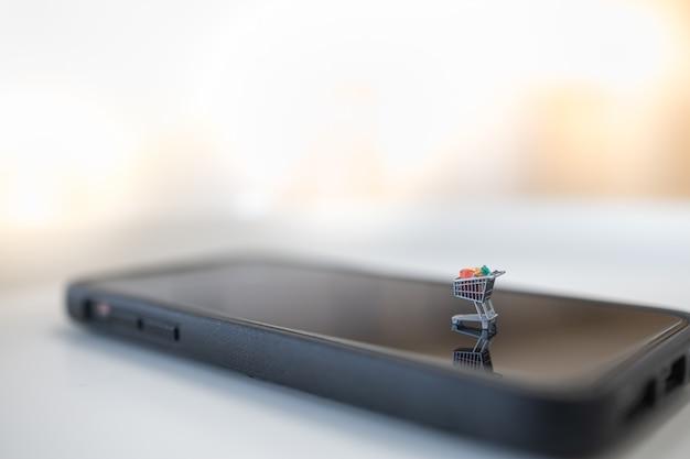 Ciérrese para arriba de figura del miniagure del carro de la compra / de la carretilla en el teléfono móvil elegante con el espacio de la copia. Foto Premium