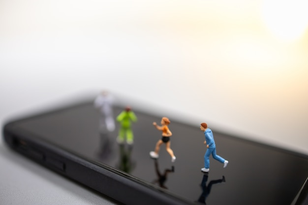 Ciérrese para arriba del grupo de figura miniatura del corredor que se ejecuta en la pantalla del teléfono móvil elegante. Foto Premium