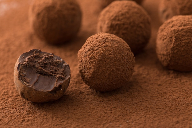Ciérrese para arriba del grupo de trufas de chocolate negras apetitosas cubiertas en polvo del cacao. Foto Premium