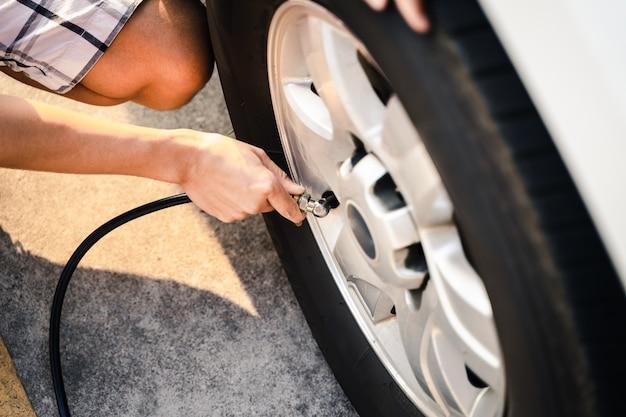 Ciérrese para arriba del hombre asiático que infla el neumático en la gasolinera. Foto Premium