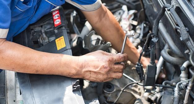 Ciérrese para arriba de la mano del mecánico que sostiene la llave delante del motor de coche con la capilla abierta. Foto Premium