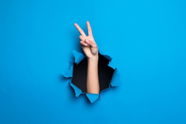 Ciérrese para arriba de la mano de la mujer con gesto de paz a través del agujero azul en la pared de papel. Foto gratis