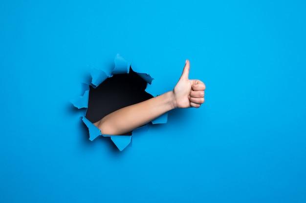 Ciérrese para arriba de la mano de la mujer con los pulgares encima del gesto a través del agujero azul en la pared de papel. Foto gratis
