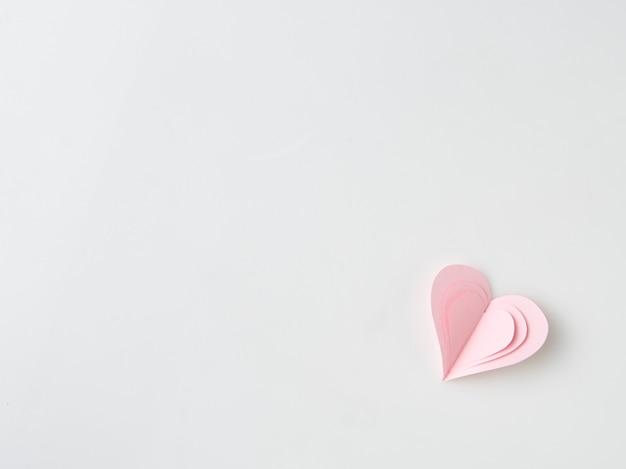 Ciérrese para arriba en las manos femeninas que llevan a cabo los presentes rosados de un corazón para el día de san valentín, cumpleaños, madre Foto Premium