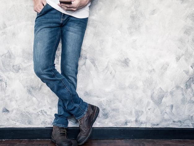 Cierrese Para Arriba De Las Piernas Del Hombre En Pantalones Vaqueros Y Botas En Piso De Madera Foto Premium