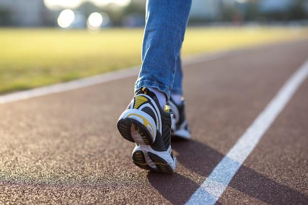 Ciérrese para arriba de pies de la mujer en zapatillas de deporte y tejanos en carril para correr en pista de deportes al aire libre. Foto Premium