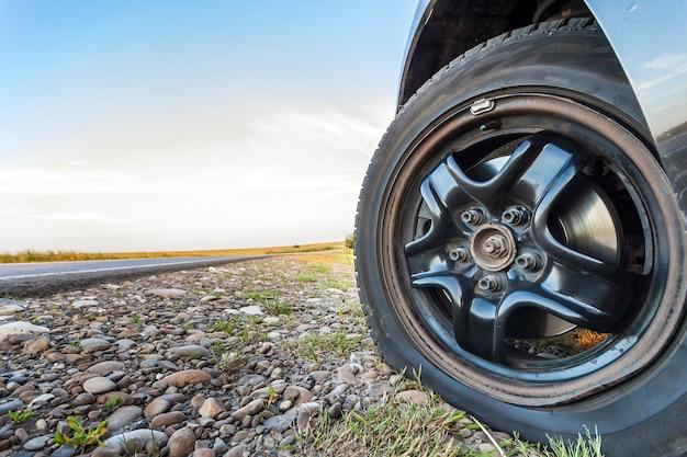 Ciérrese para arriba de la rueda pinchada en un coche en el camino de la grava. Foto Premium