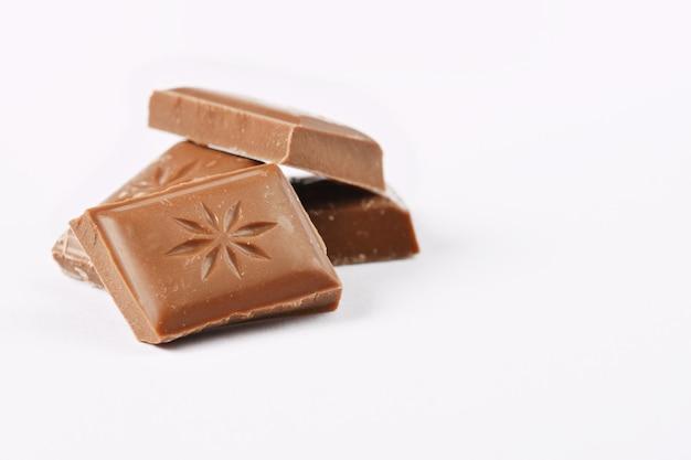 Ciérrese encima de una barra de chocolate aislada en el fondo blanco. Foto gratis