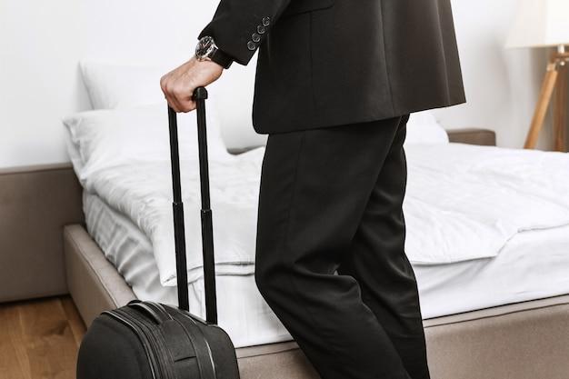 Ciérrese encima del detalle del hombre de negocios elegante en el traje negro que sostiene la maleta en las manos que van a salir de la habitación de hotel y volar a casa en avión de viaje de negocios. Foto gratis