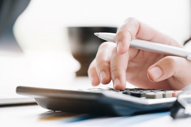 Ciérrese encima de la empresaria que usa la calculadora y la computadora portátil para las finanzas de las matemáticas en el escritorio de madera en oficina Foto Premium