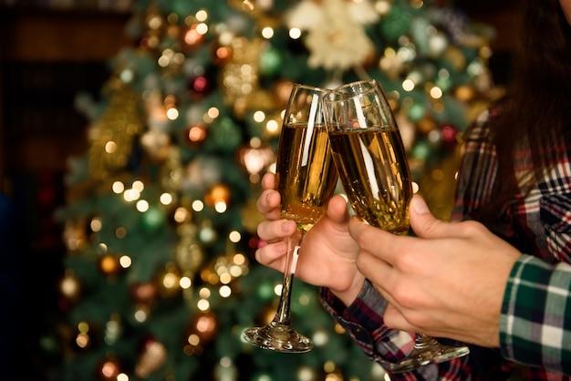 Ciérrese encima de la foto de dos personas que sostienen copas de champán en navidad. Foto Premium