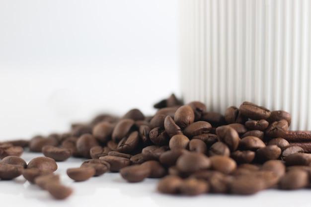 Ciérrese encima de los granos de café y de la taza blanca aislados en el fondo blanco. Foto Premium
