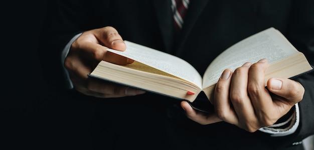 Ciérrese encima del hombre que lee un libro, muestra una mano del primer y un libro. Foto Premium