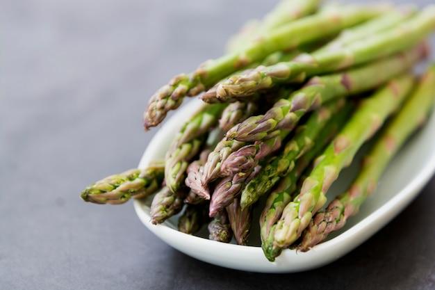 Ciérrese encima de las lanzas del espárrago sobre fondo oscuro con el espacio de la copia. concepto de comida sana y vegana. comer limpio. Foto Premium