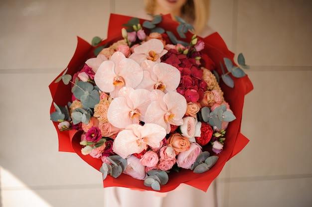 Ciérrese encima de la muchacha en el abrigo que sostiene un ramo de flores rosadas y rojas adornadas con el verdor Foto Premium