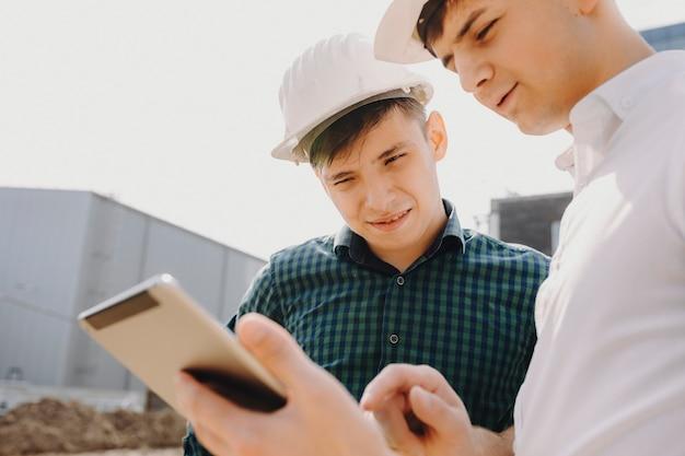 Ciérrese encima del retrato del arhitect joven que escucha a su dueño dónde comenzar a trabajar en el edificio. Foto Premium