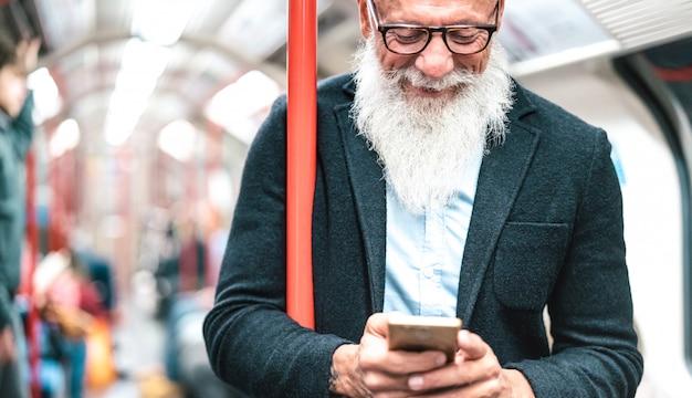Ciérrese encima del retrato del hombre barbudo del inconformista que usa el teléfono móvil inteligente en metro Foto Premium