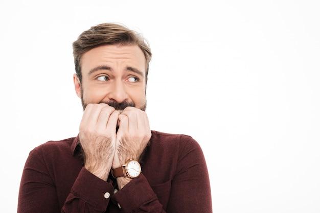Ciérrese encima del retrato de un hombre barbudo joven asustado Foto gratis