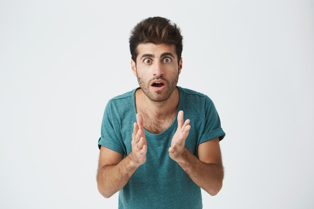 Ciérrese encima del retrato del individuo italiano maduro en camiseta azul casual, tomados de la mano, se congeló en una actitud en anticipación durante el partido de hockey. lenguaje corporal. Foto gratis