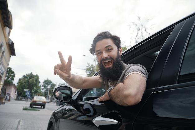 Ciérrese encima del retrato lateral del hombre feliz que conduce el coche Foto gratis