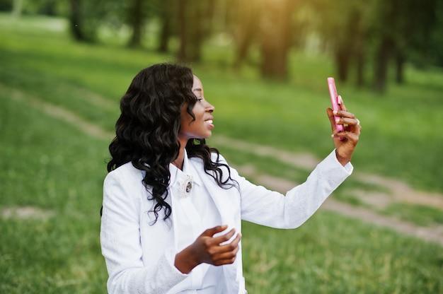 Ciérrese encima del retrato de la muchacha afroamericana negra elegante que toma el selfie con el teléfono móvil rosado Foto Premium