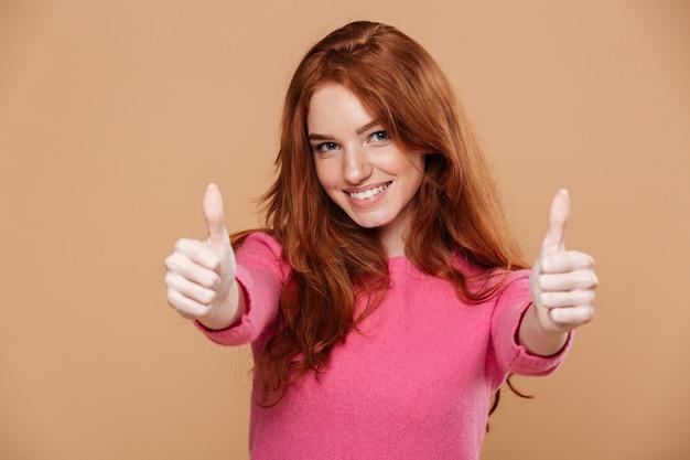 Ciérrese encima del retrato de una muchacha pelirroja bonita alegre con los pulgares para arriba Foto gratis
