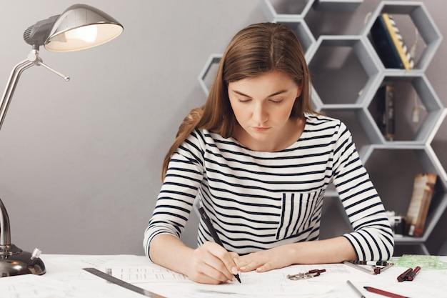 Ciérrese encima del retrato de la muchacha seria joven del arquitecto que hace su trabajo en el espacio acogedor del coworking, mirando el papel con la expresión seria e infeliz. Foto gratis