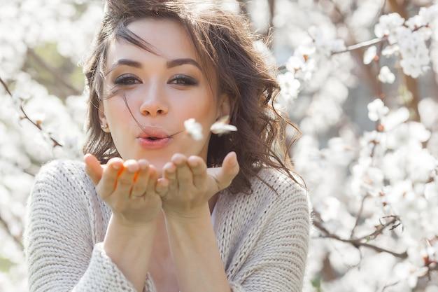 Ciérrese encima del retrato de la mujer hermosa joven en la primavera. chica joven atractiva con flores. maquillaje de primavera modelo. Foto Premium