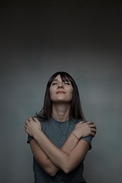 Ciérrese encima del retrato de la mujer que se abraza Foto gratis