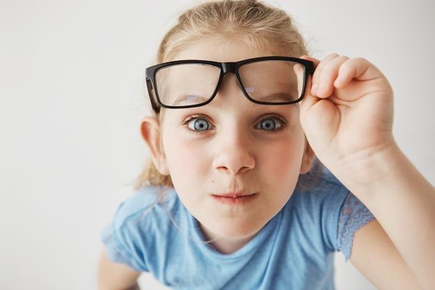 Ciérrese encima del retrato de la niña curiosa con los ojos azules grandes que se colocan cercanos y, sosteniendo los vidrios con la mano. Foto gratis